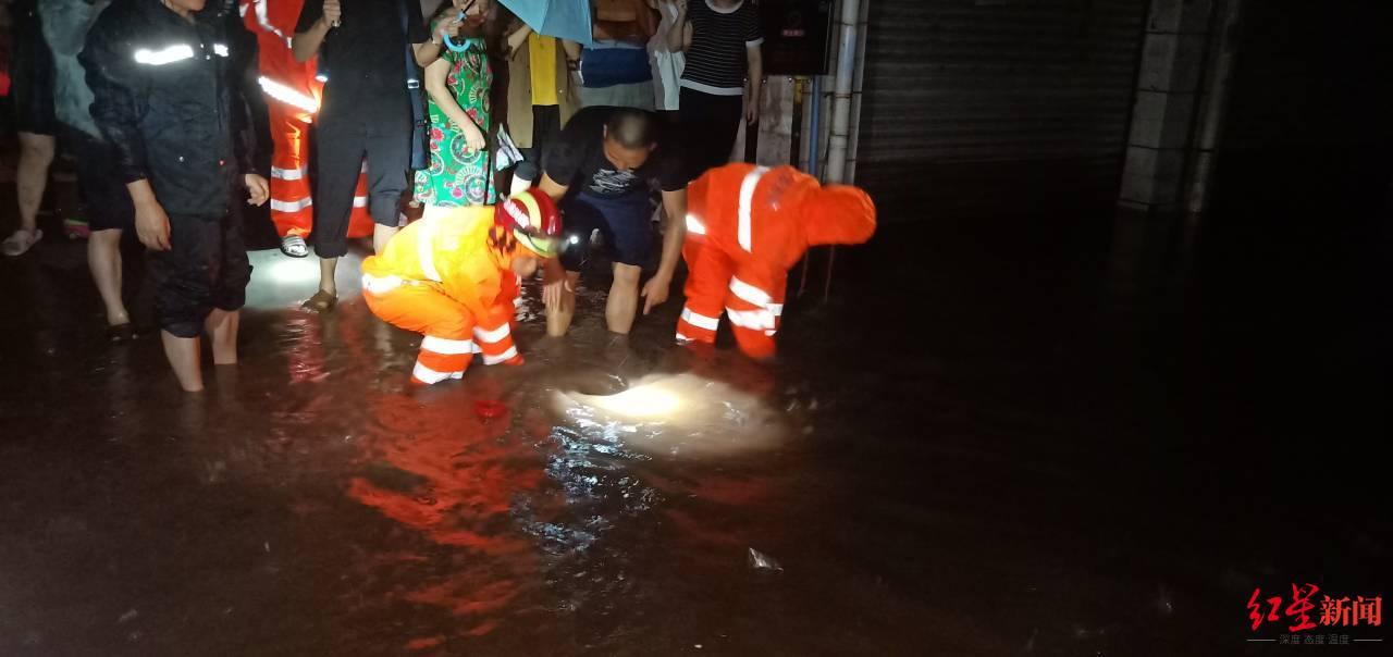 ↑在发生积水的街道,消防员疏通下水道排水。