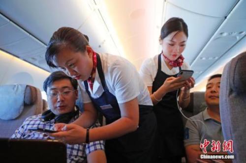 资料图:乘务员们在客舱内为旅客调试机上上网功能。中新社记者 殷立勤 摄