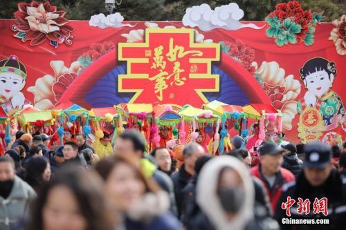 2月9日,游客在北京八大处公园庙会上游玩,观看传统民间花会表演。 盛佳鹏 摄