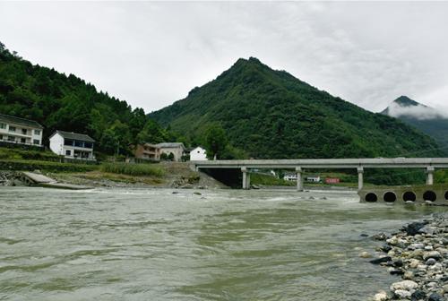 来往车辆从刚建成的桥上通过。新桥下方就是被洪水冲毁的漫水桥。