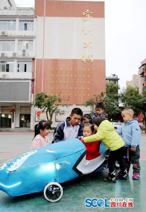 """小朋友们在观看于勇俊的新能源""""汽车"""" 王超明 摄"""