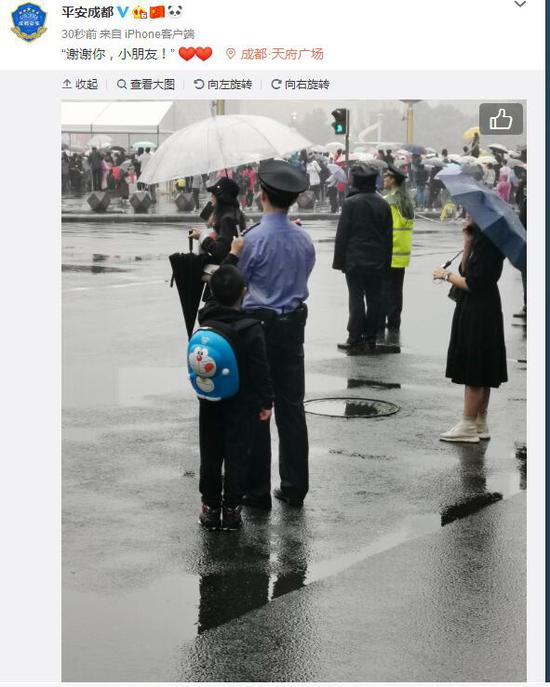 天府广场升国旗仪式上,有小朋友自发为执勤民警打伞。图自:@平安成都