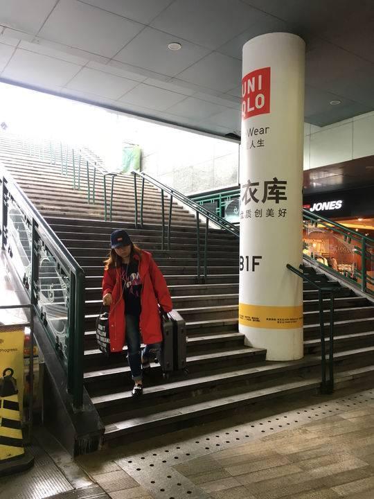 乘客拿着行李箱走下楼梯