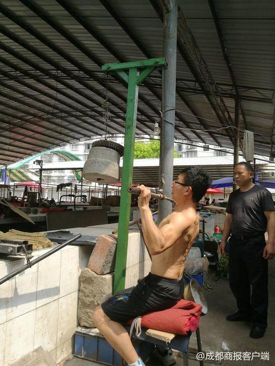 ▲肖世虎正在自制健身器材上锻炼