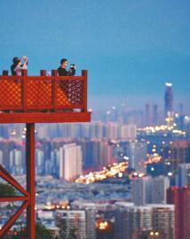 晨曦中,市民在龙泉山上远眺城市美景。
