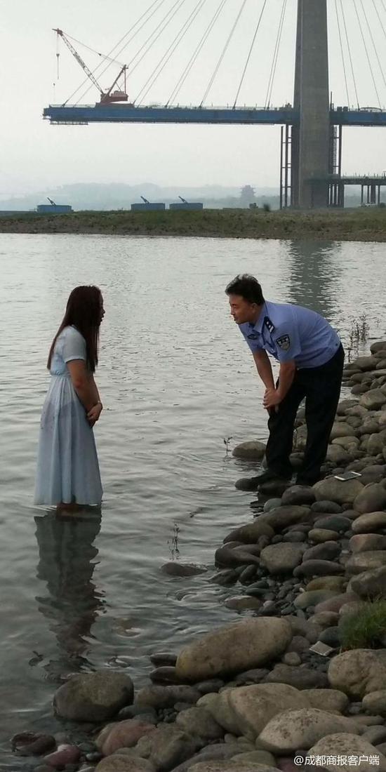 ▲胖警官站在江中的石堆上与女子沟通,她的背后是一片深水区
