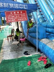 安徽省马鞍山市当涂县威尼士水上乐园的充气滑梯破旧脏乱,现场 工作人员一个在玩手机,一个闭目养神。 新华社发