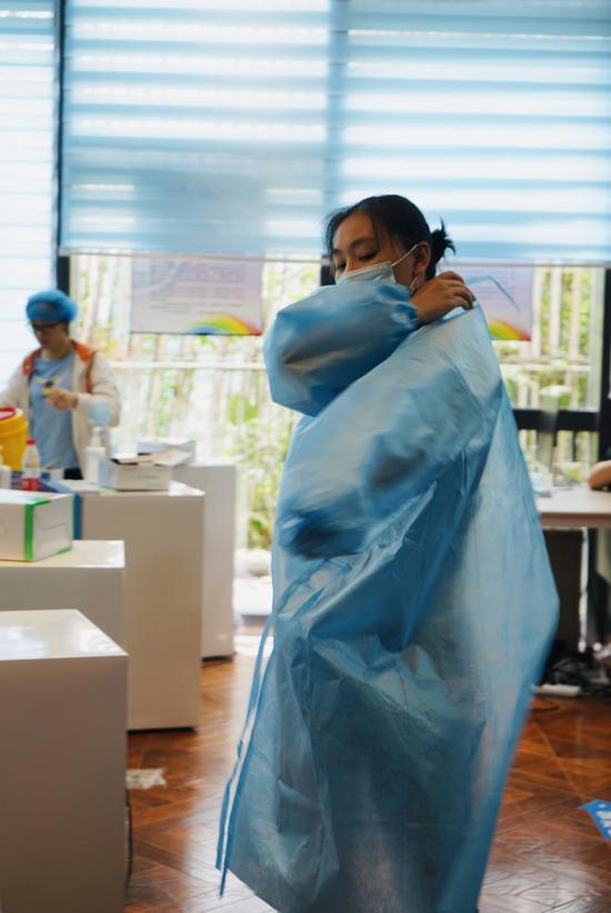 锦江区沙河街道新冠疫苗临时接种点,医护人员冯倩换上工作服。魏冯摄。