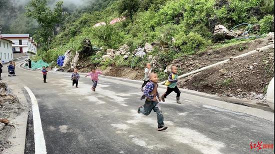 ↑阿布洛哈村的通村公路建成,小孩在奔跑玩耍