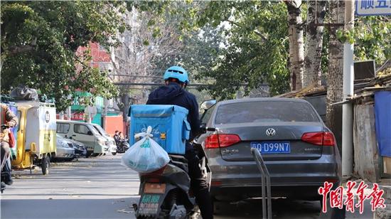 11月12日,在北京市丰台区,一位外卖小哥的配送箱上拴着一个塑料袋。   中青报·中青网见习记者 赵丽梅/摄