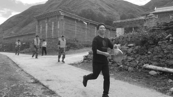 马伍萨(右前)在村上组织防灾演练。