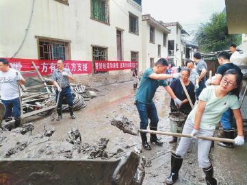 """""""8·20""""强降雨特大山洪泥石流灾害发生后,汶川县财政局干部职工带头为当地群众清淤。"""