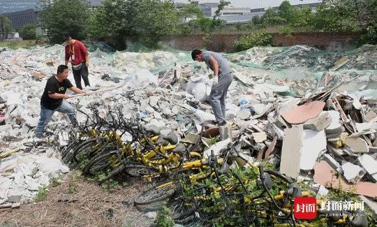 """工作人员挖出上百辆被""""活理""""的共享单车。"""