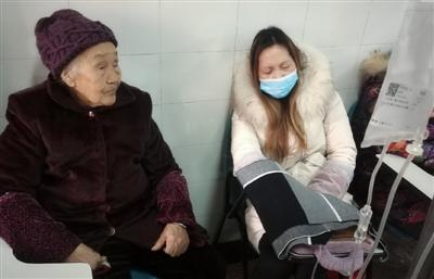 邓明琼在90多岁的母亲陪伴下输液