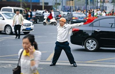 2014年5月2日,蜀都大道上,交通协管员童元成正在奋力指挥交通 成都商报记者 王效 摄