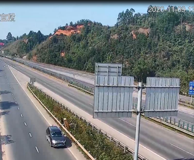 越野车上的两人正在高速路绿化带中搬运电瓶车。(视频截图)