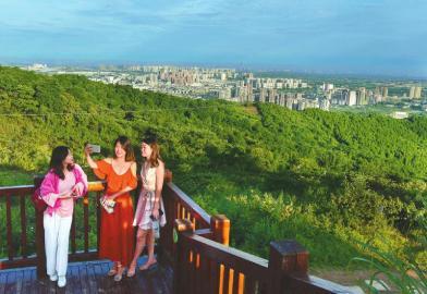 年轻人在山顶鸟瞰山城一体的美景。