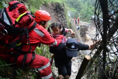 救援队沿着陡峭山路转移滞留人员
