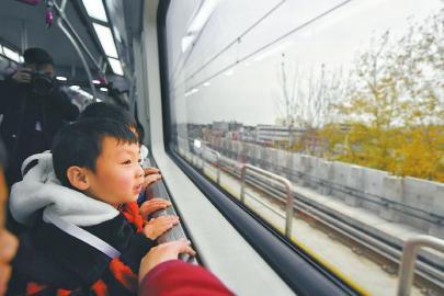 试乘的孩子们好奇地看着车窗外的风景。 本报记者 杨树 摄