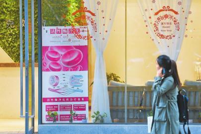 4月11日,成都宏济巷的一家美容院,一位市民在张望活性酶净化治疗广告。本报记者杨树摄