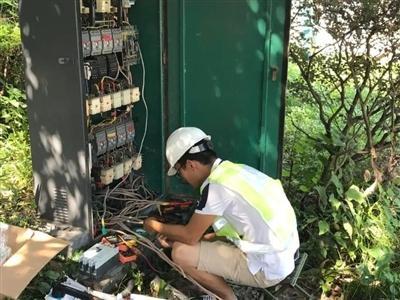 工作人员正在对南湖片区的配电柜进行检查