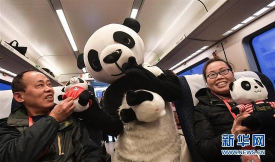 """在成都西至雅安的C6651次列车上,""""熊猫""""与旅客们互动。 新华社记者薛玉斌摄"""