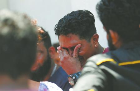 4月21日,在斯里兰卡首都科伦坡,遇难者亲属掩面哭泣。