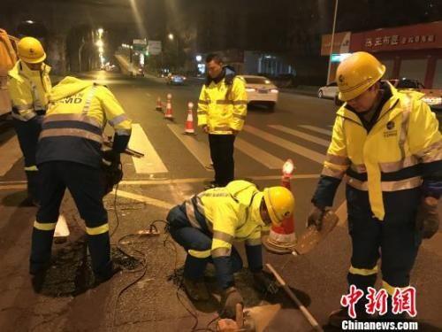 李良驹与工友在夜间维护道路。 吕杨 摄
