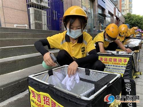 外卖配送员正在对餐箱进行消毒擦拭