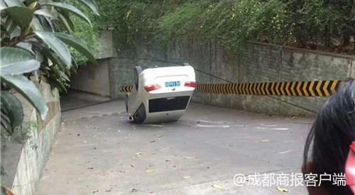 宜宾女司机开车入库误上台阶翻车 疑因避让前方红色宝马