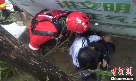 图为一处围墙被积水冲垮塌,墙上广告牌掉下砸到一名学生。 刘贵 摄