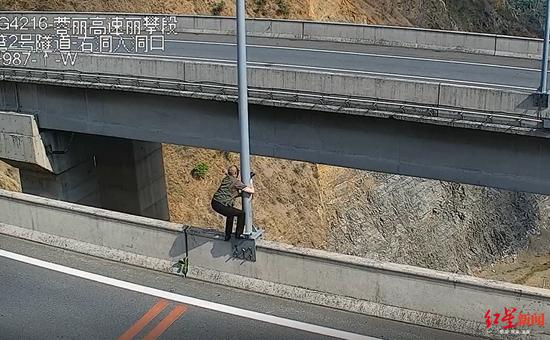 男子丽攀高速应急车道停车爬60米大桥护栏拍照 记6分罚200