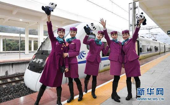 12月28日,在雅安站,乘务员在列车前合影 新华社记者薛玉斌摄