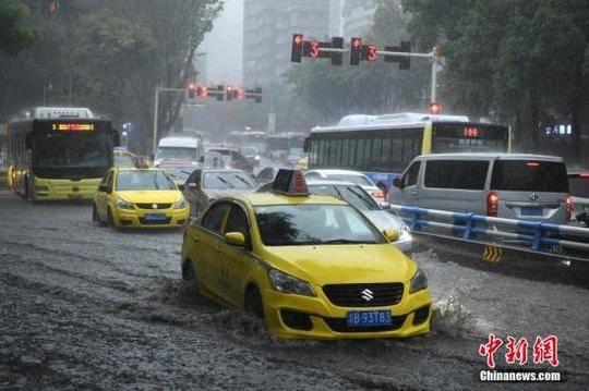 资料图:车辆缓慢通过积水路段。陈超 摄