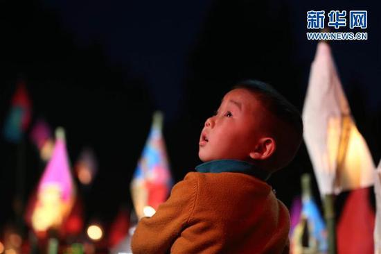 """3月1日,在四川省南充市嘉陵区三会镇,一位小朋友仰望""""蛴蟆灯""""。新华社记者张帆摄"""