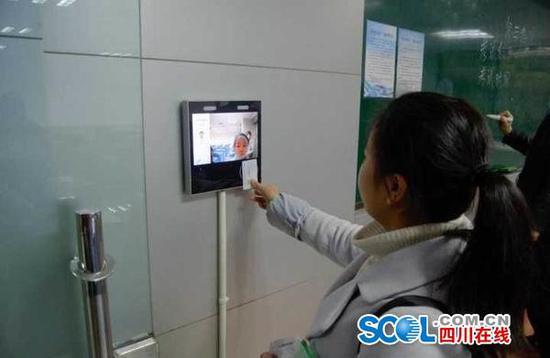考生通过人脸识别系统进考场。