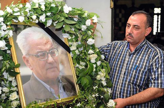穆罕默德•阿萨德(右),相框中是他的父亲哈立德•阿萨德,帕尔米拉博物馆原馆长,2015年因拒绝向IS透露考古文物保存地,被砍头杀害。图片来源:新华社