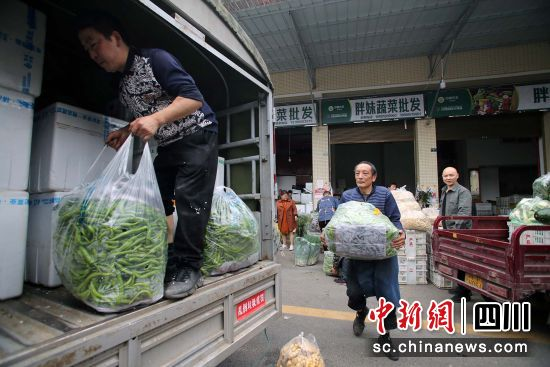 蔬菜批发商将新鲜蔬菜搬运上车 王磊 摄