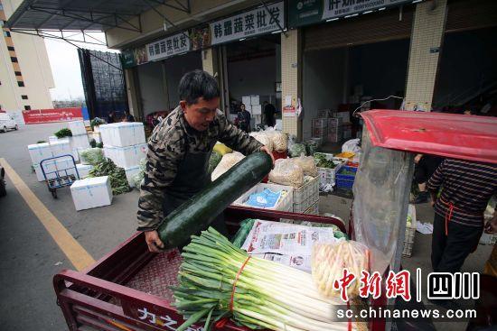 一名采购商将刚购买的蔬菜放在车上 王磊 摄