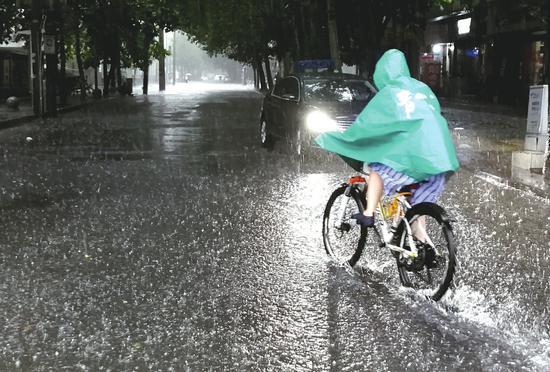 7月11日,成都市民在风雨中出行。