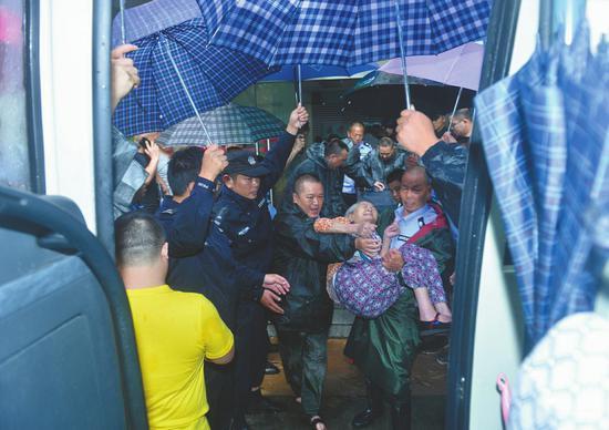 民警和城管队员们用雨伞搭出一条避雨通道,将老人们护送上车。