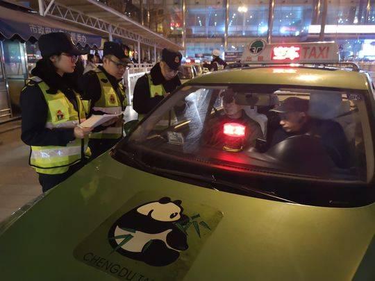 20日晚,成都市交通运输行政执法总队执法人员在火车北站执法检查出租车。