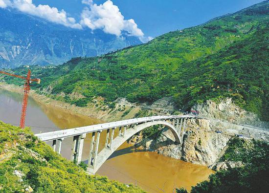 9月1日,凉山州金阳县对坪镇金沙江大桥上,工人正在对桥面进行最后施工作业。大桥的完工,标志着四川最后一个溜索改桥项目建成。本报记者吴传明摄