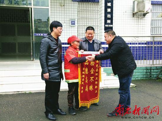 杨兵向范登星赠送锦旗,?#34892;?#22905;拾金不昧的行为。