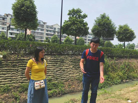 廖圳龙重返施救现场,其身后便是老人溺水的排水渠。
