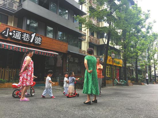 居民在泡桐树街上乘凉玩耍。