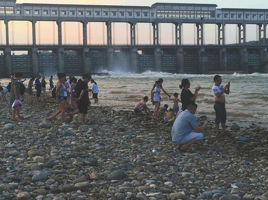 上方就是泄洪口,沙滩上的游人玩兴不减。