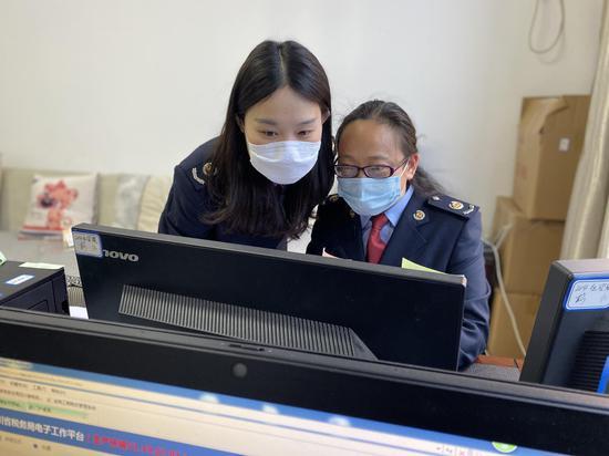 王普婷与同事一起核对享受优惠行业企业数据