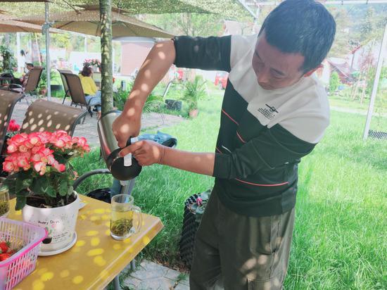 张发平为来农庄的游客倒茶。