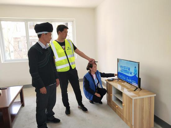 中国移动四川公司工作人员为迁入安置点的老乡调测宽带电视